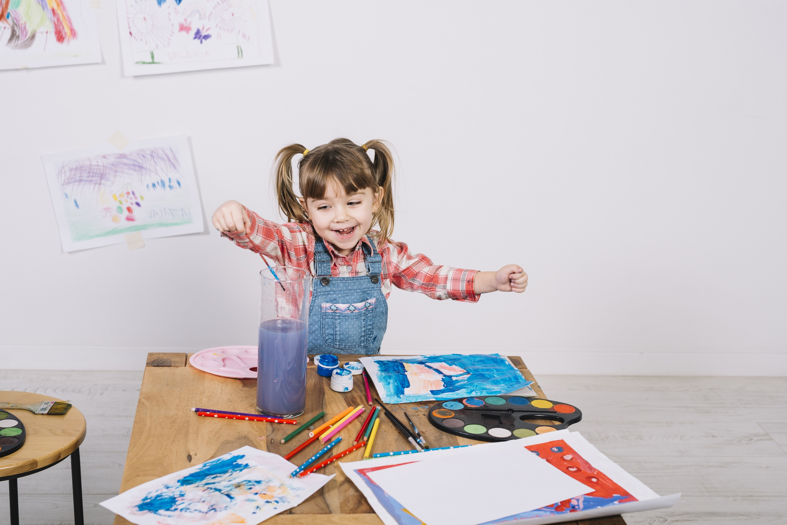Girl happily painting using paintbrush and watercolour