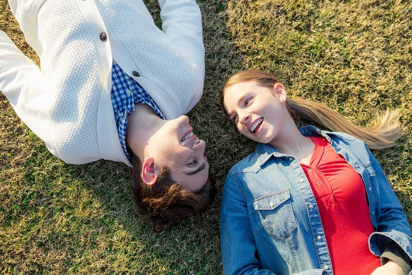 A boy and a girl laying on the ground together dating in love