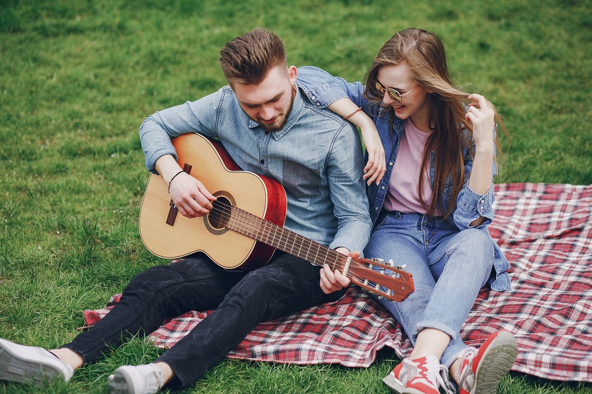 Beautiful girl with handsome boy sitting in a park on a blanket with guitar