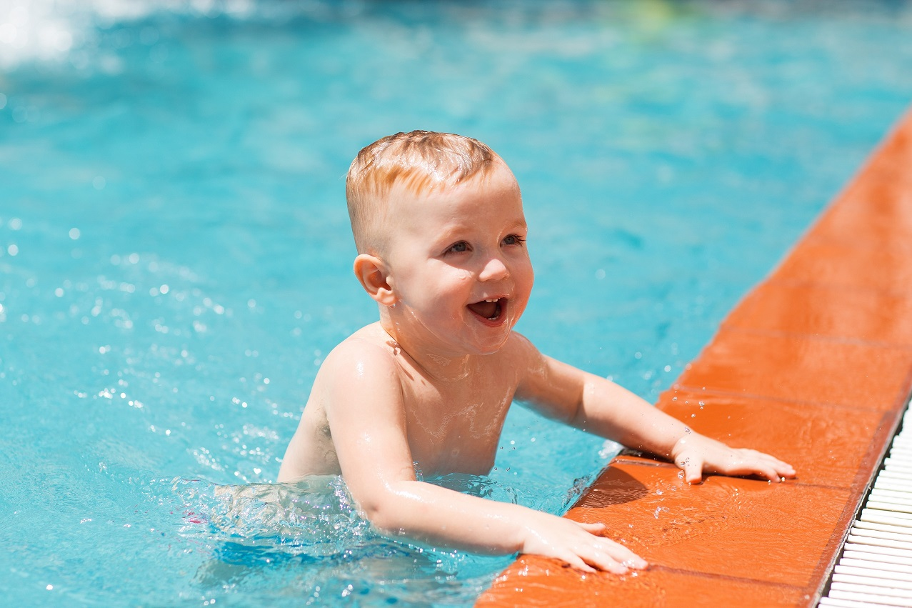 Portrait of happy little Caucasian boy swimming in outdoor pool and smiling. Summer vacation, sport, health and childhood concept
