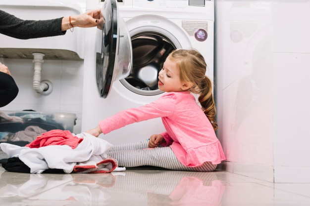 girl helping mom with laundry