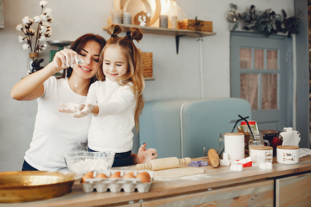 girl preparing meal with mom