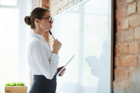 Young pensive woman with highlighter and notepad standing by blank whiteboard