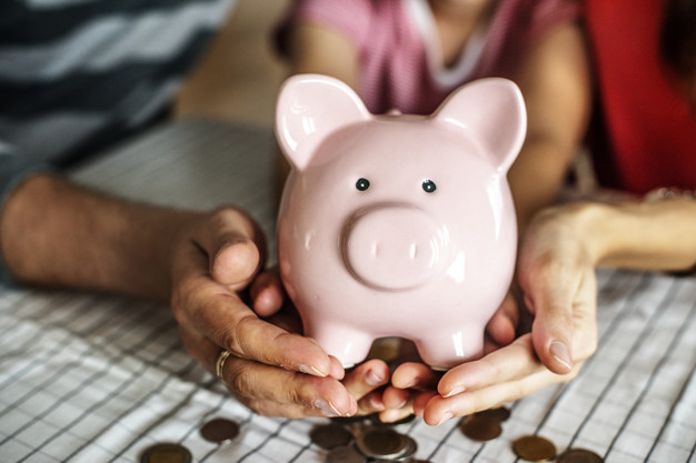 woman and man holding piggy bank with child