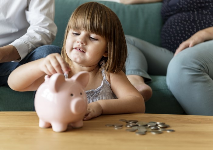 girl putting coins in her piggy bank