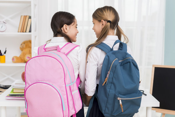 two girls carrying backpacks
