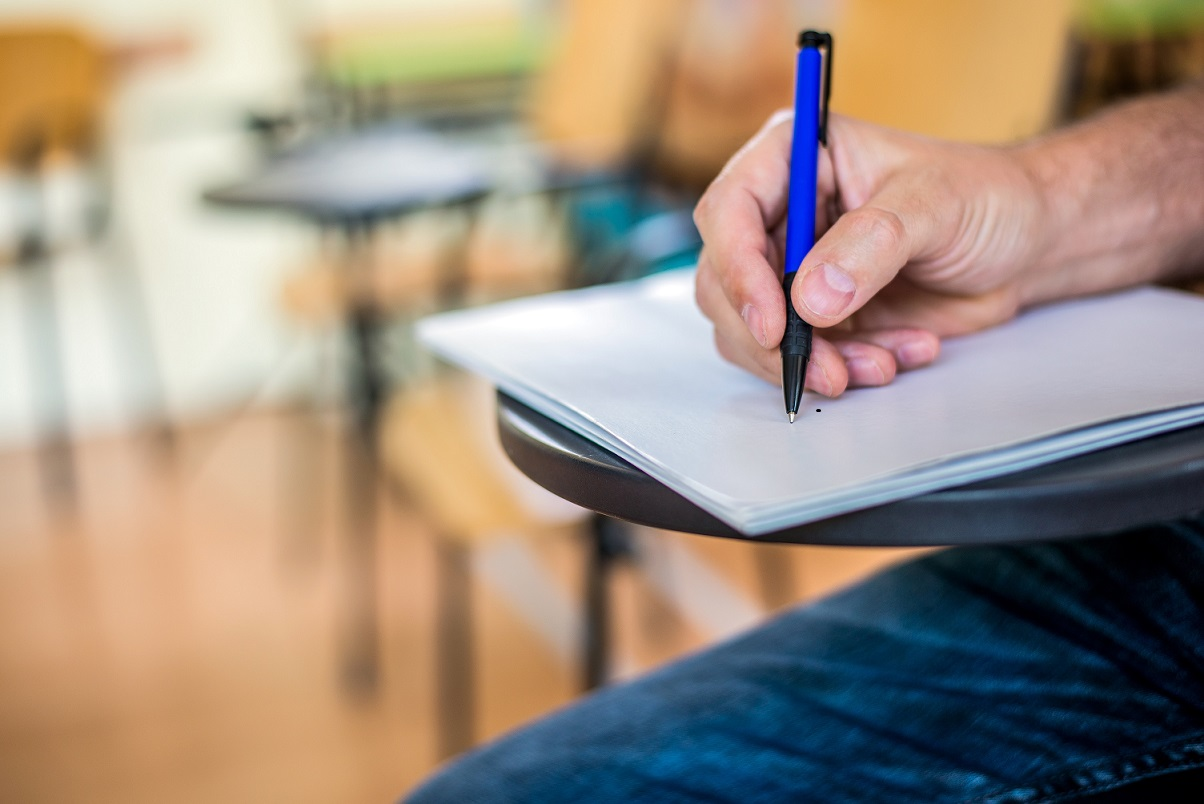 A man is writing/signing on a paper. Focused on a hand with pen. undergraduate student holding pencil and sitting on row chair doing final exam attending in examination room or classroom.university student.