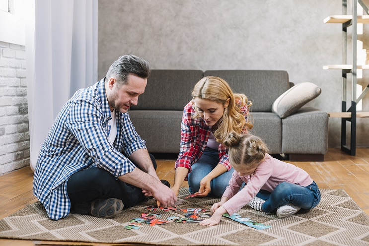 child solving jigsaw pattern with parents