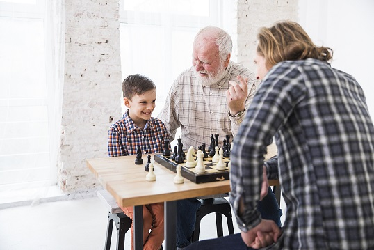 child learning and playing chess with grandfather and father