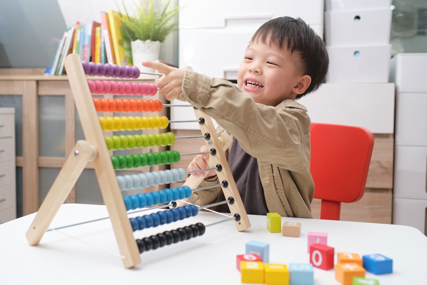 Cute little asian kindergarten 4 years old boy using the abacus with beads and wooden brick with numbers to learn how to count indoor at home, Use an Abacus to teach maths for little kids concept