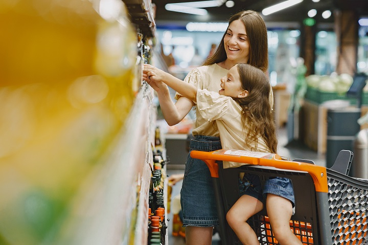 Family at the supermarket. Woman in a brown t-shirt. People choose products. Mother with daughter.