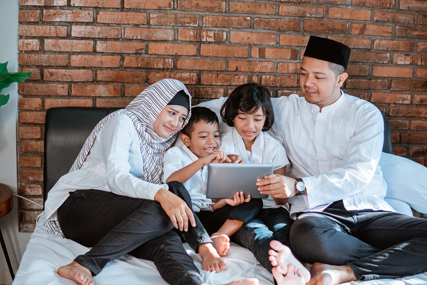 happy asian family on ramadan kareem using tablet pc for social interaction with friend