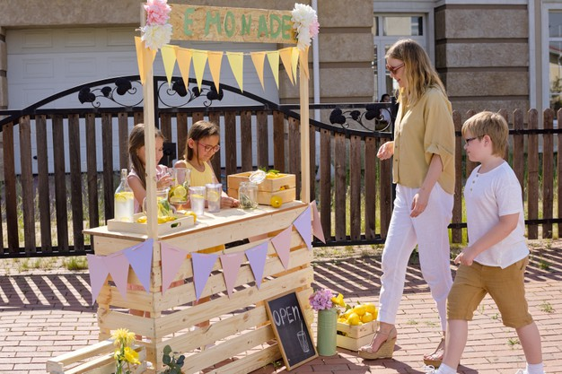 children at a lemonade stand selling and buying