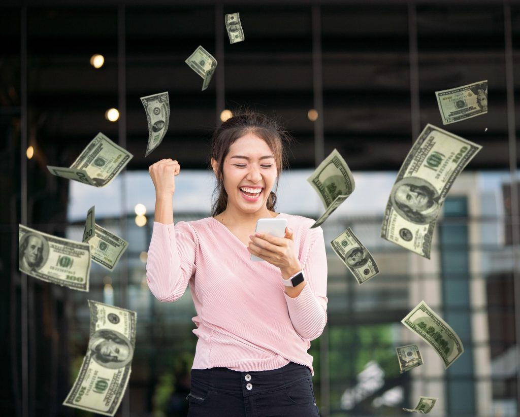 Girl receive happy notification on phone with money falling from sky