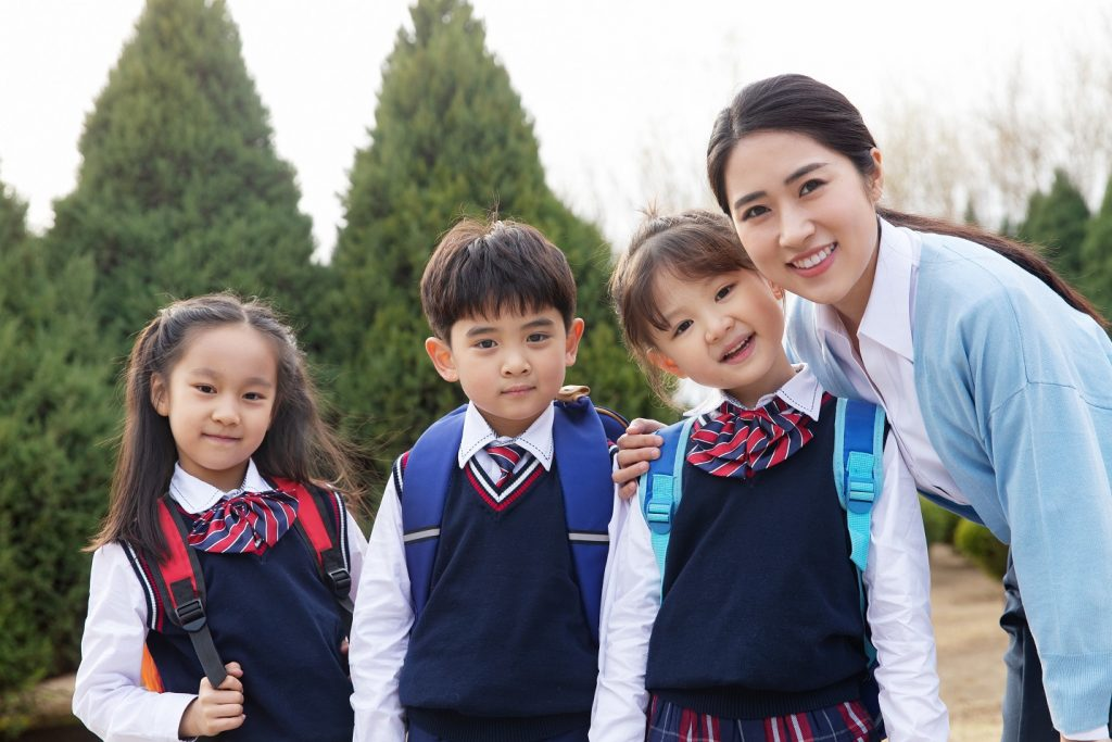 Preschool students in uniform and a teacher